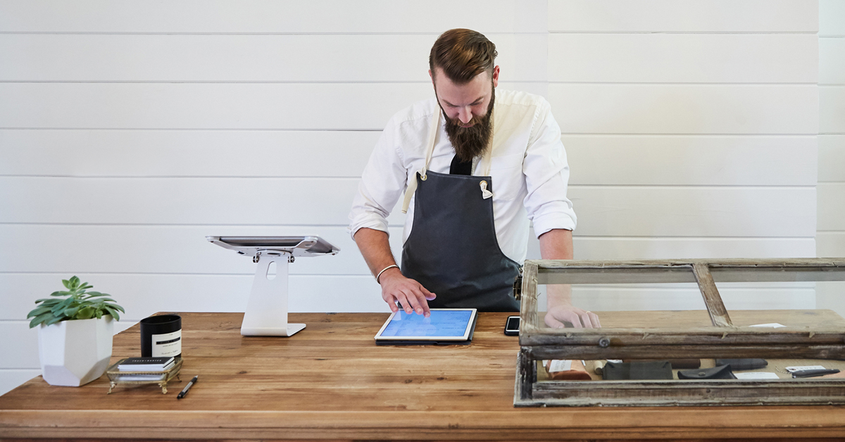 Butcher with iPad and empty fridge, representing online sales made