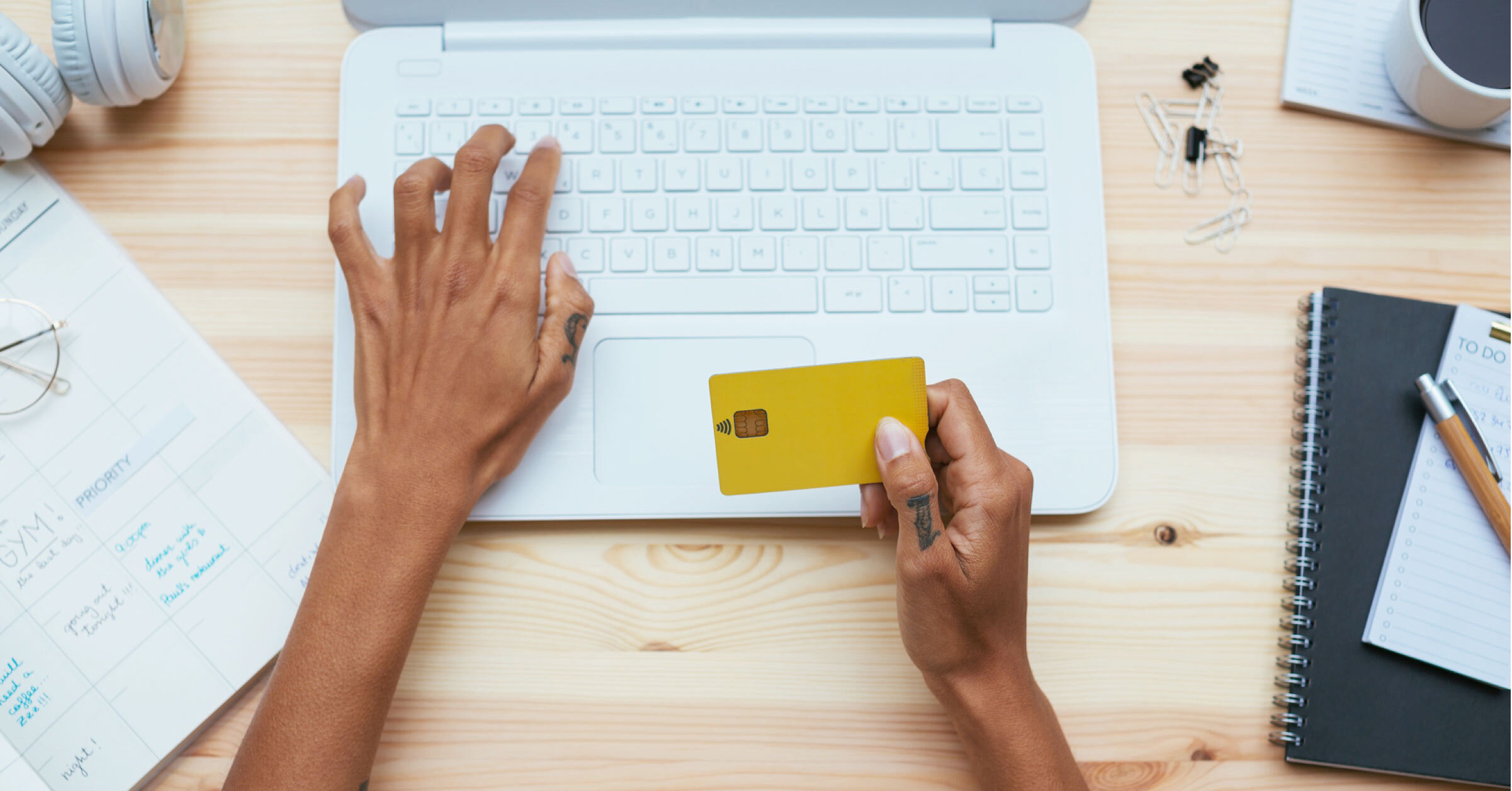Customer at a laptop holding card to complete an online purchase